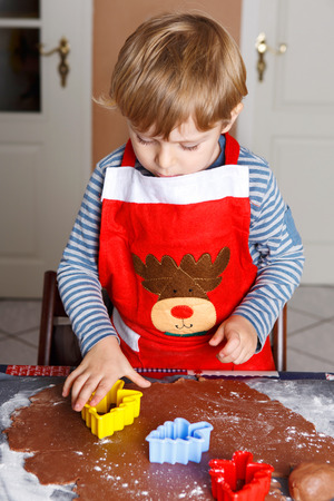 Little boy baking ginger bread trees for Christmas in homes kitchen photo