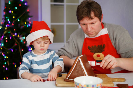 Man and his little son preparing a gingerbread cookie house at christmas time photo