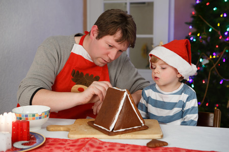 Father and little child preparing a gingerbread cookie house at christmas time photo