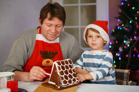Little kid boy and his dad having fun with baking a gingerbread cookie house at christmas time, homes kitchen photo