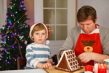 Happy family of two: Dad and his little son having fun with baking a gingerbread cookie house at christmas time, homes kitchen photo
