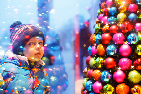 holiday lights display: Adorable little boy looking through the display window at Christmas decoration in the shop