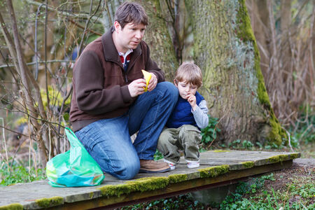 Little kid boy and his dad playing together with colorful paper boats by a river on spring or autumn day. Creative leisure with kids. photo