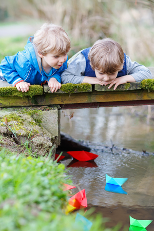 Two little brothers playing together with colorful paper boats by a river on spring or autumn day. Creative leisure with kids. photo