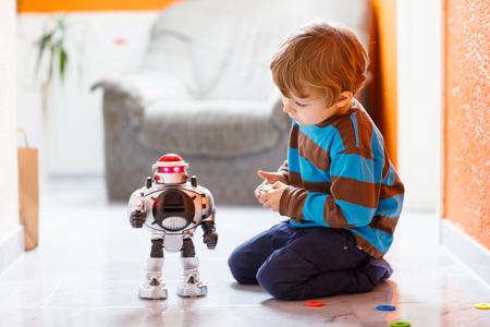 Pequeño muchacho rubio que juega con el juguete robot en casa, interior