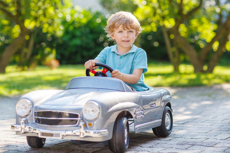 1: Little preschool boy driving big toy car and having fun, outdoors.