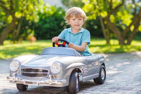 divertirsi: Piccolo ragazzo prescolare guida grossa auto giocattolo e divertirsi, all'aperto. Archivio Fotografico