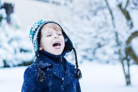 neige qui tombe: Portrait de bambin garçon en vêtements d'hiver avec des chutes de neige Banque d'images