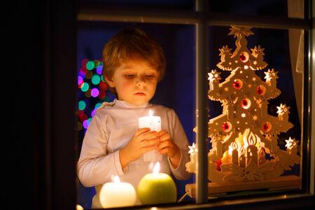 velas de navidad: El niño pequeño pie por la ventana en tiempo de Navidad y la celebración de vela. Con coloridas luces de árbol de navidad en el fondo, foco selectivo.