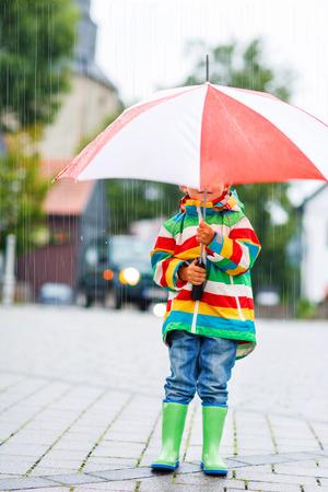 niños caminando: Niño lindo que recorre en ciudad y esconderse bajo el paraguas rojo, vestido con capa de lluvia de colores y botas verdes al aire libre en día de lluvia Foto de archivo
