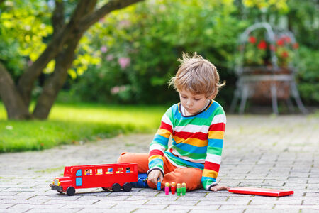 cute blond kid boy playing with red school bus and toys in summer garden. photo