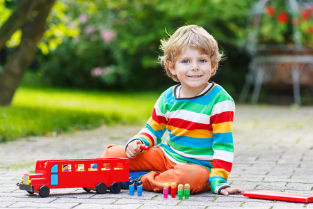 Little adorable preschool boy playing with red school bus and toys in summer garden on warm sunny day. photo