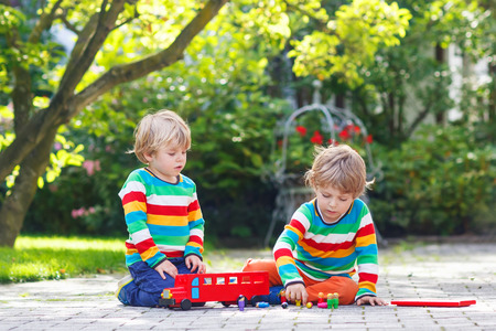 Two little boy friends in colorful clothing with stripes playing with red school bus and toys in summer garden on warm sunny day.