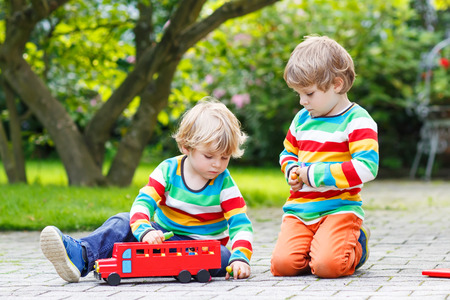 Two little friends in colorful clothing with stripes playing with red school bus and toys in summer garden on warm sunny day. Learning to play and communicate together. photo