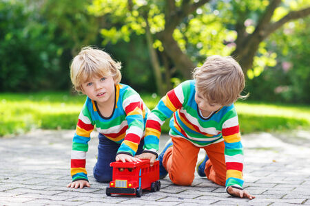 Two little kids in colorful clothing with stripes playing with red school bus and toys in summer garden on warm sunny day. Learning to play and communicate together. photo