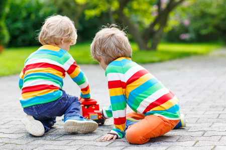 Two siblings, kid boys in colorful clothing with stripes playing with red school bus and toys in summer garden on warm sunny day. Learning to play and communicate together. photo