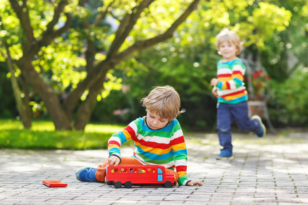 Little kid boy playing with red school bus and toys in summer garden. Another boy on background photo