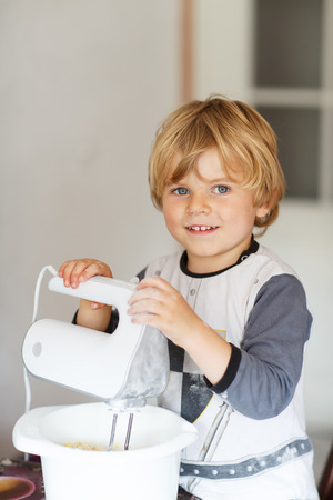 Adorable little boy helping and baking pie in home''s kitchen, indoor. Stock Photo - 32764437