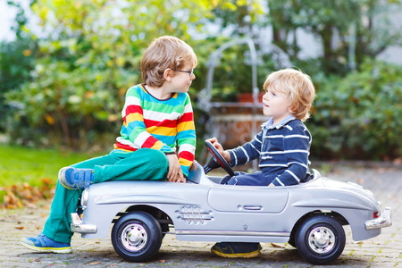 Two happy kids playing with big old toy car in summer garden, outdoors. Siblings and friends on warm day.