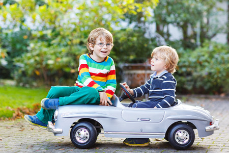 game drive: Two happy kids playing with big old toy car in summer garden, outdoors. Siblings and friends on warm day.