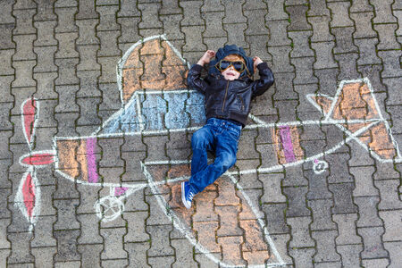 creativity:  Funny little child of four years having fun with airplane picture drawing with chalk.