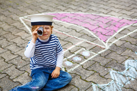 Creative leisure for children: Funny little child of four years having fun with ship or boat picture drawing with chalk. photo