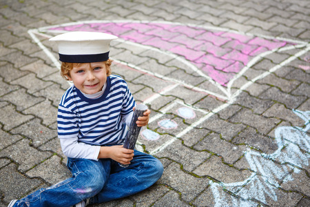 Creative leisure for children: Funny little kid boy of four years having fun with ship or boat picture drawing with chalk. photo