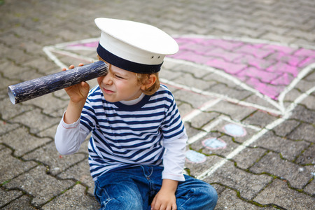 Creative leisure for children: Funny little  preschool child of four years having fun with ship or boat picture drawing with chalk. photo