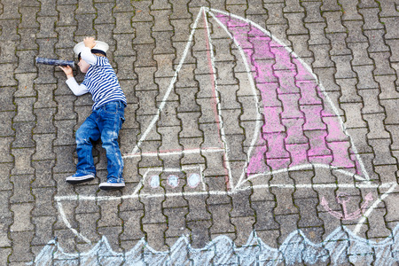 Creative leisure for children: Funny little boy of four years having fun with ship or boat picture drawing with chalk. photo