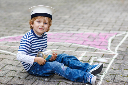 Creative leisure for children:  Happy little child of four years having fun with ship or boat picture drawing with chalk, outdoors game. photo