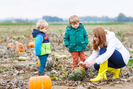 Family of three: Mother and two little sons having fun on pumpkin patch photo