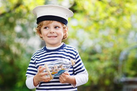 skipper: Happy kid in skipper uniform playing with toy ship against green tree summer background Stock Photo