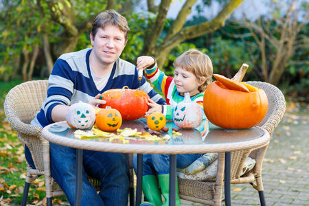 Young dad and his little kid son making jack-o-lantern for halloween in autumn garden, outdoors. Family having fun together photo