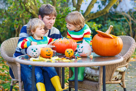 Young father and his two little sons making jack-o-lantern for halloween in autumn garden, outdoors. Happy family of three having fun together photo