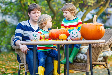 Dad and his two little sons making jack-o-lantern for halloween in autumn garden, outdoors. Happy family of three having fun together photo
