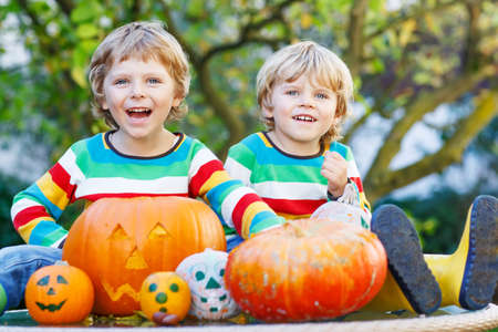 Two little kid brother boys making jack-o-lantern for halloween in autumn garden, outdoors. Happy family having fun together