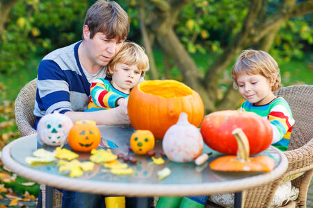 Young dad and his two little sons making jack-o-lantern for halloween in autumn garden, outdoors. Family having fun together photo