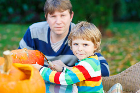 Young dad and his little son making jack-o-lantern for halloween in autumn garden, outdoors. Family having fun together. Selective focus on boy. photo