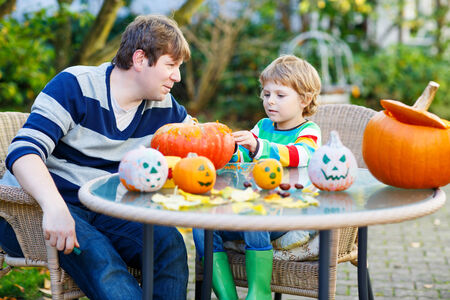 Adorable kid boy and his father making jack-o-lantern for halloween in autumn garden, outdoors. Family having fun together photo