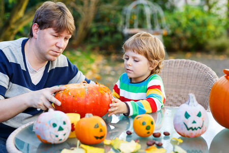 Adorable little child and his father making jack-o-lantern for halloween in autumn garden, outdoors. Family having fun together photo