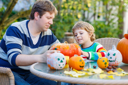 Cute kid boy and his father making jack-o-lantern for halloween in autumn garden, outdoors. Family having fun together photo
