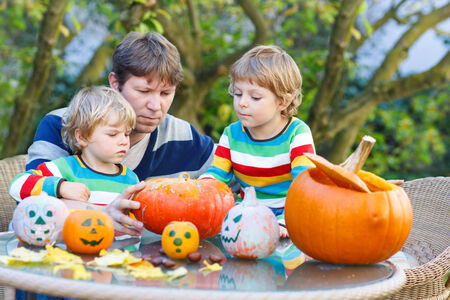 Young father and his two little sons making jack-o-lantern for halloween in autumn garden, outdoors. Happy family of three having fun together