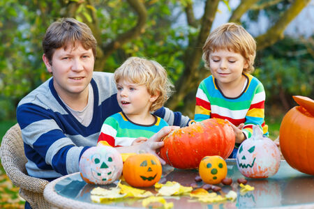 Young father and his two kid boys making jack-o-lantern for halloween in autumn garden, outdoors. Happy family of three having fun together