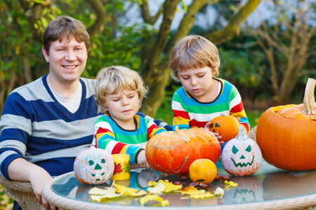 Young father and two sibling boys making jack-o-lantern for halloween in autumn garden, outdoors. Happy family of three having fun together