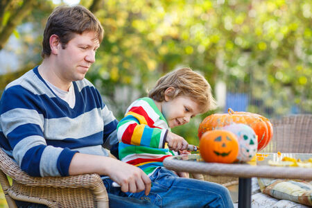 Young dad and his little son making jack-o-lantern for halloween in autumn garden, outdoors. Family having fun together photo