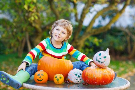 Little kid boy making jack-o-lantern for halloween in autumn garden, outdoors. Having fun on sunny warm october day photo