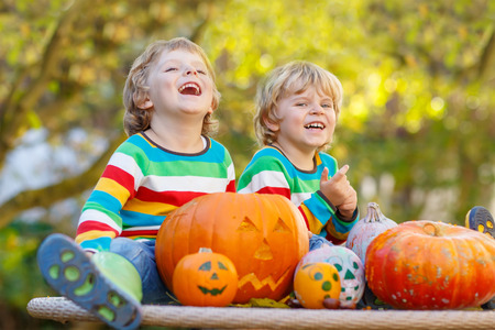 Two little sibling boys making jack-o-lantern for halloween in autumn garden, outdoors. Happy family having fun together