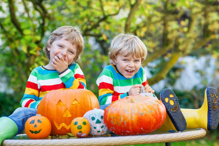 Two little twin boys making jack-o-lantern for halloween in autumn garden, outdoors. Happy family having fun together photo
