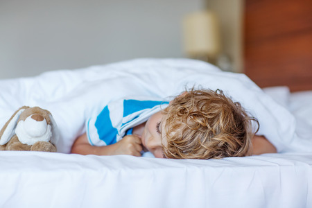 Adorable child sleeping and dreaming in his white bed with toy.