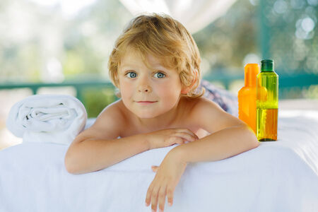 spa  thai massage: Adorable little blond kid relaxing in spa with having massage. Stock Photo